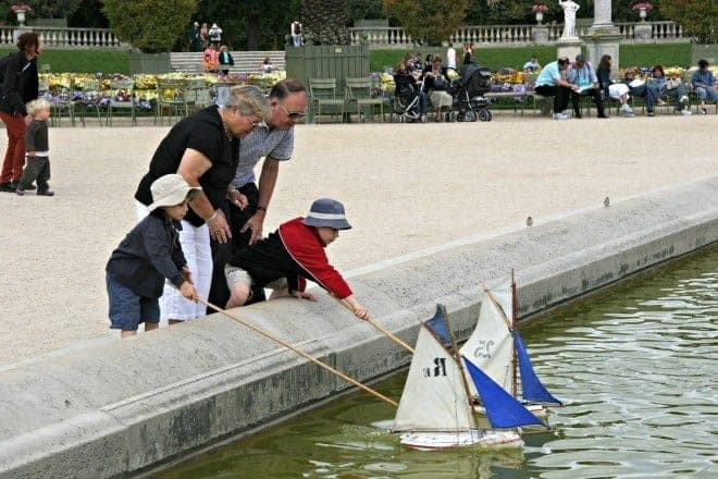 Multigenerational travel fun for all family members. Punting boats in the grande bassin in Luxembourg Gardens..