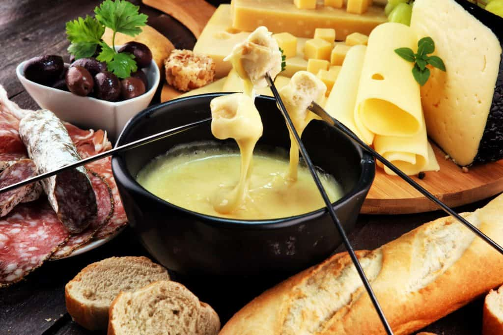 cubes of bread covered in melted cheese over fondue pot swiss foods