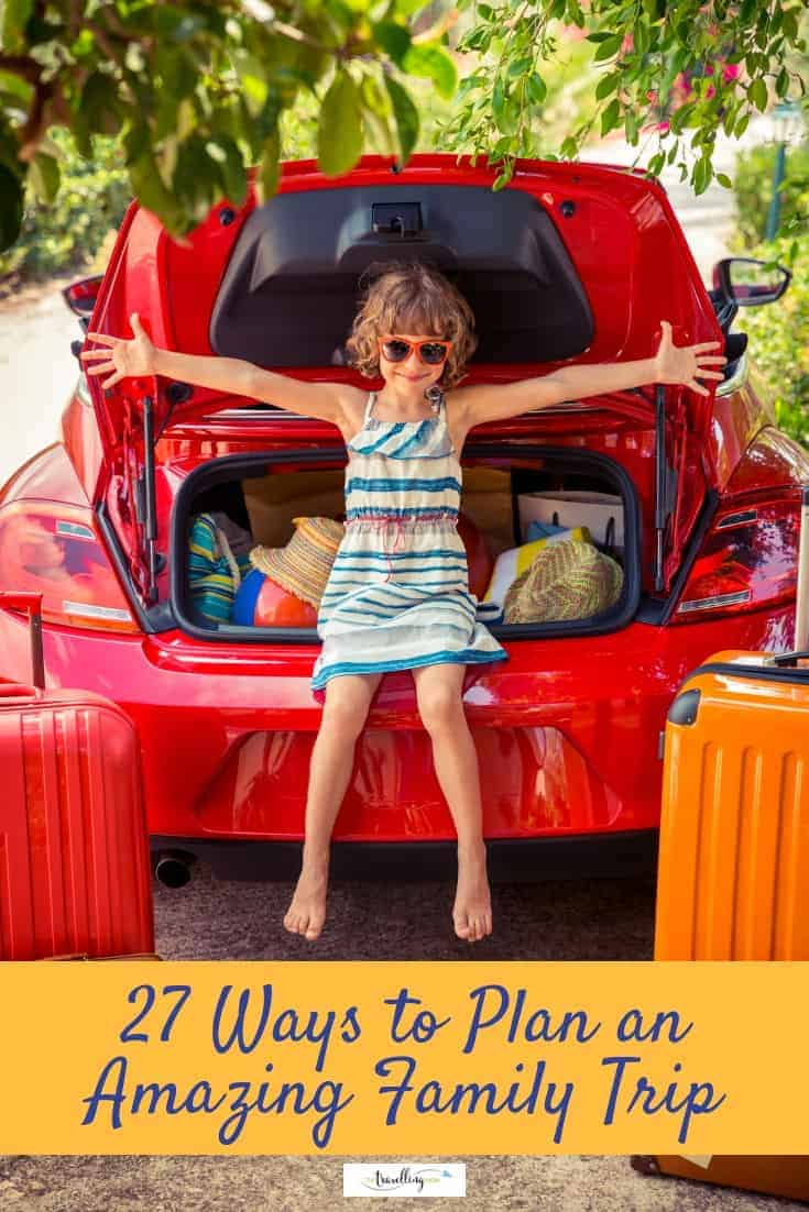 girl smiling among suitcases packed in car
