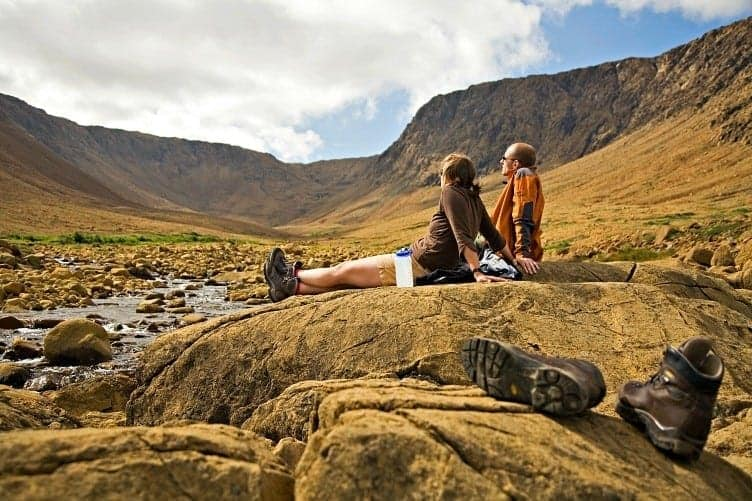 couple sitting in open field camping