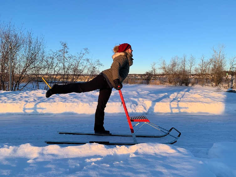 woman kick sledding at dusk in quebec in winter