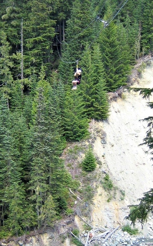 kid zip lining over creek in whistler
