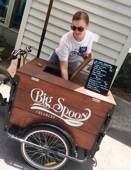 lady scooping ice cream from cart